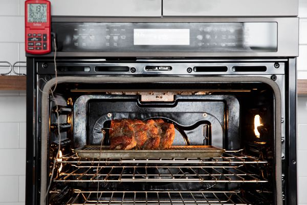 A chicken roasting inside an oven with a probe thermometer panel on the outside of the oven