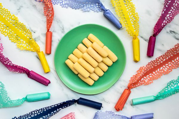 pastillas de leche on a plate surrounded by candy in intricately cut wrappers, an art form known as pabalat