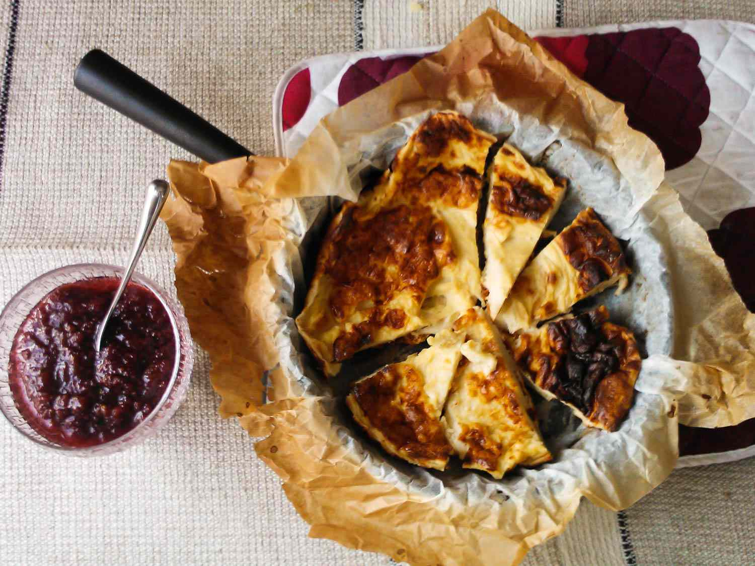 A large pannukakku in parchment paper on a skillet, with a bowl of jam next to it.