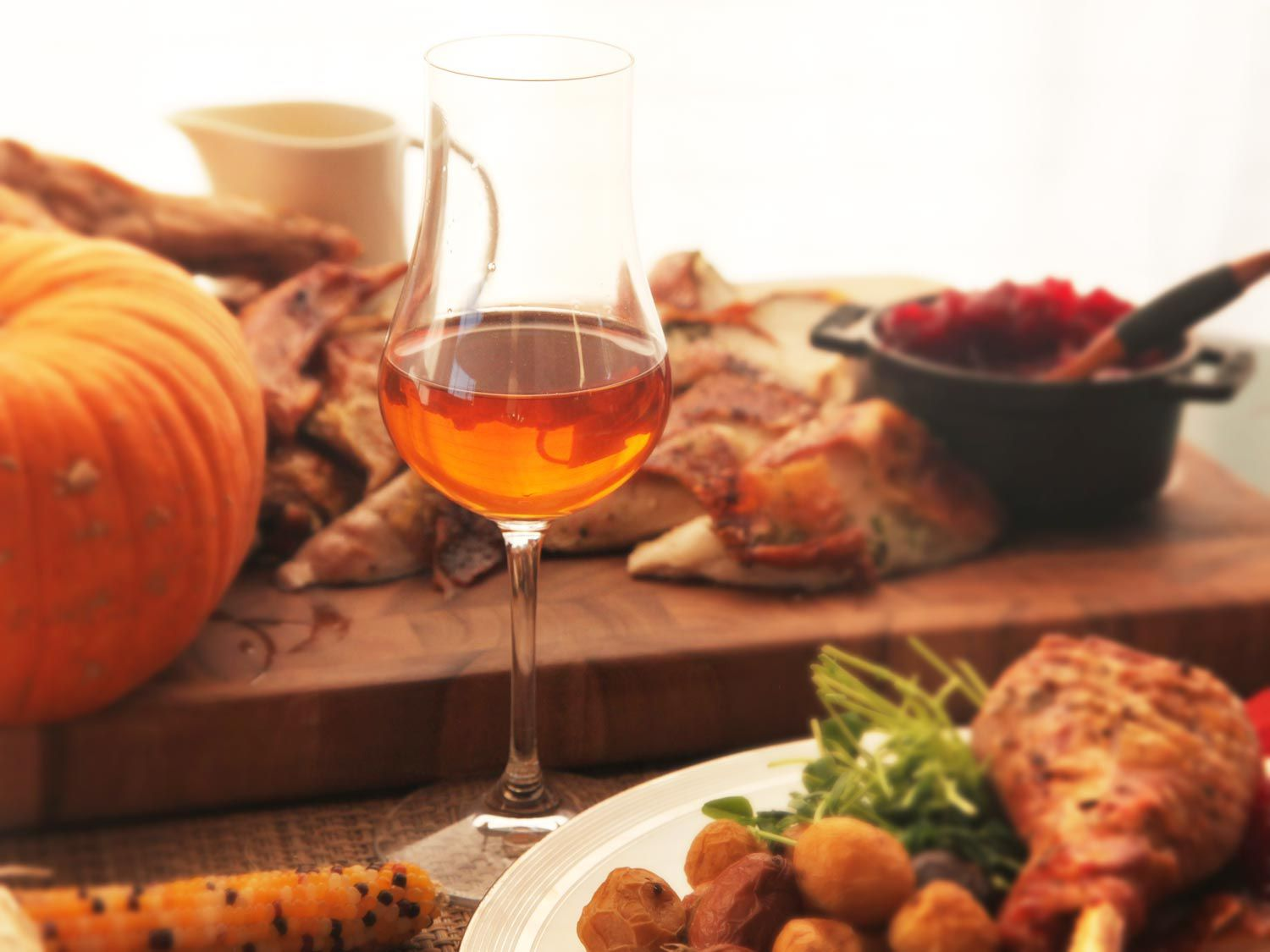 A glass of wine surrounded by a Thanksgiving spread.
