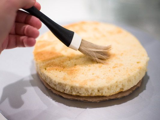 applying cake soaker with pastry brush