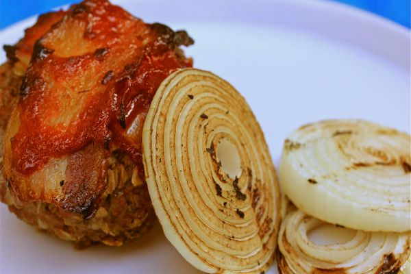 Meatloaf topped with bacon, glazed with Sriracha, and stuffed with beer cheese, served alongside grilled onions.