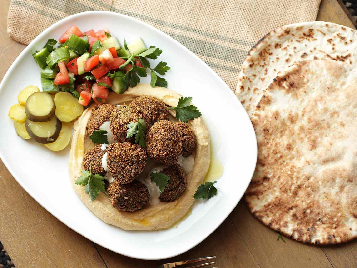 A plate of falafel and hummus with fresh herbs, pickles, and cucumber and tomato salad, next to pita bread