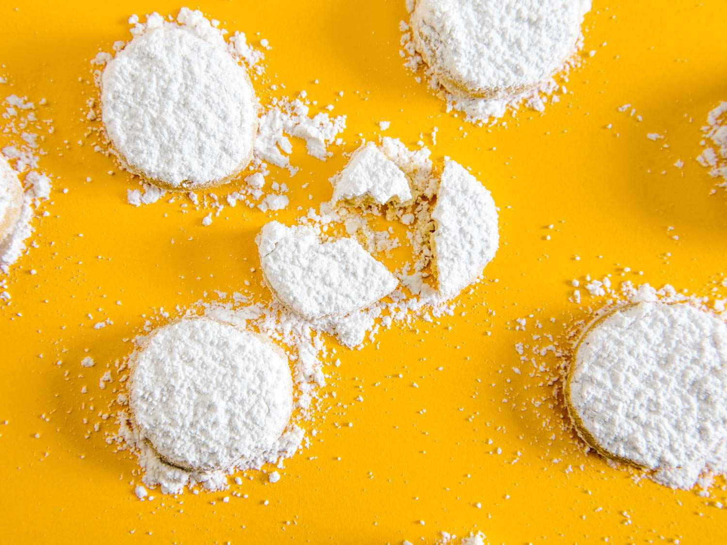 lemon meltaway cookies dusted with powdered sugar on a bright yellow background
