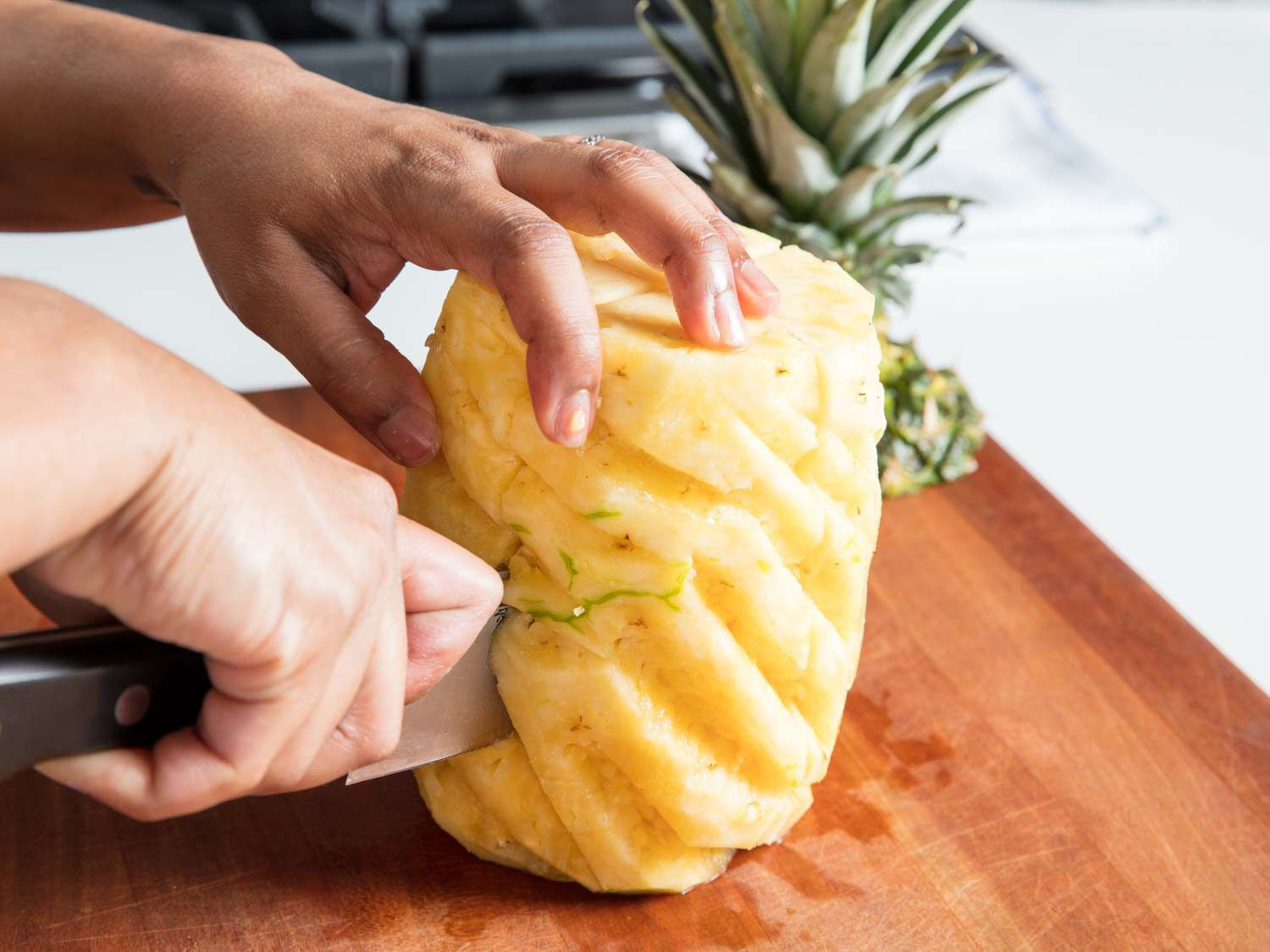 A knife slicing a pineapple into quarters.