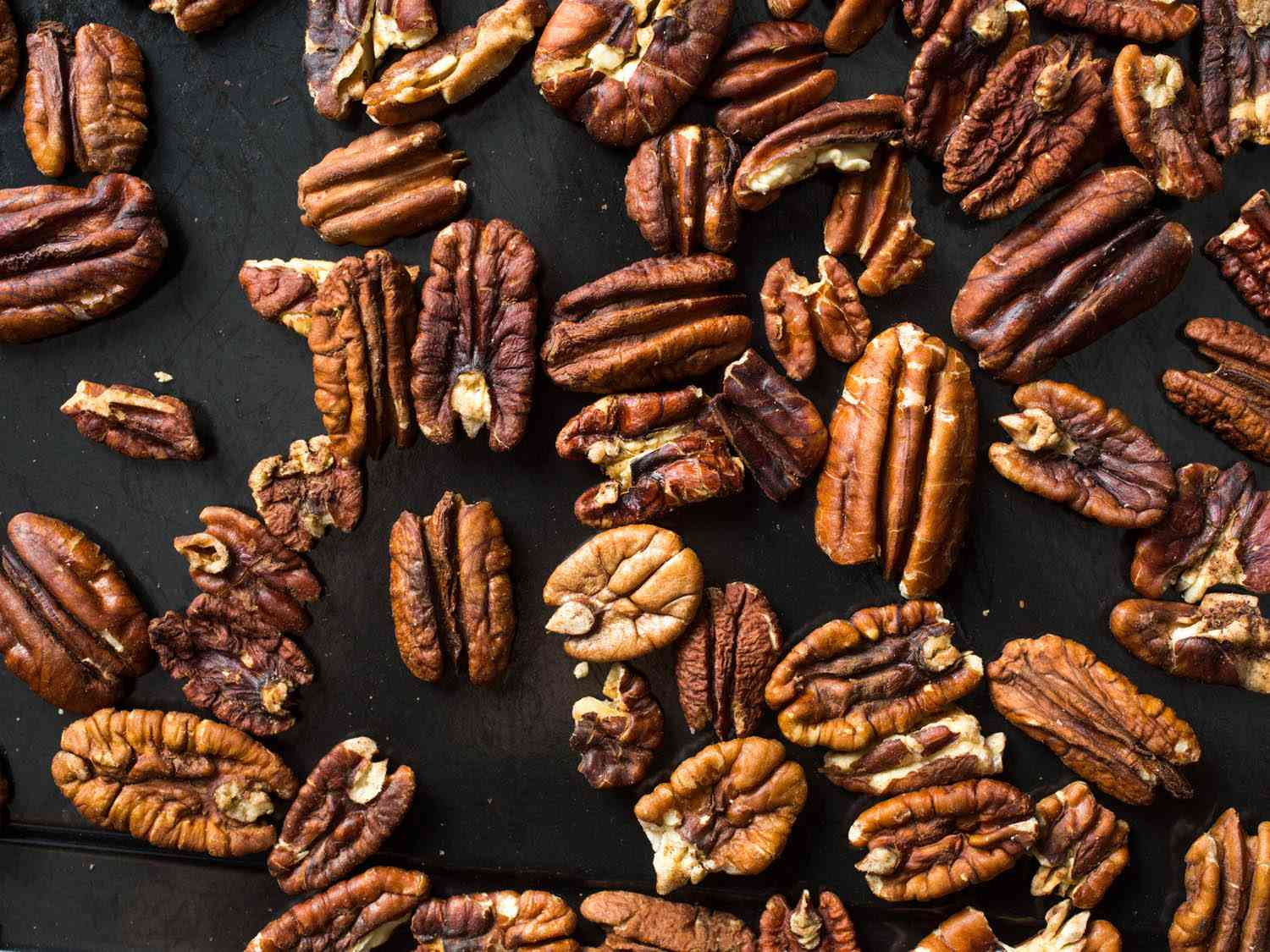 Overhead shot of raw pecan halves on a black background