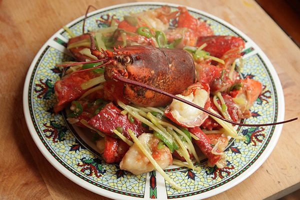 Cantonese-style lobster with ginger and scallions on a plate.