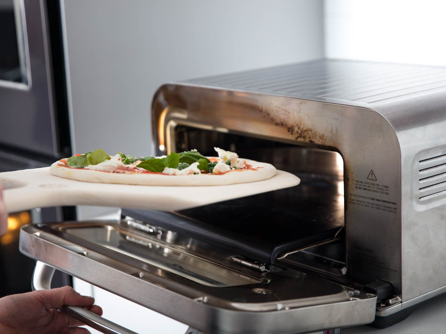 Sliding a margherita pizza into the Breville oven.