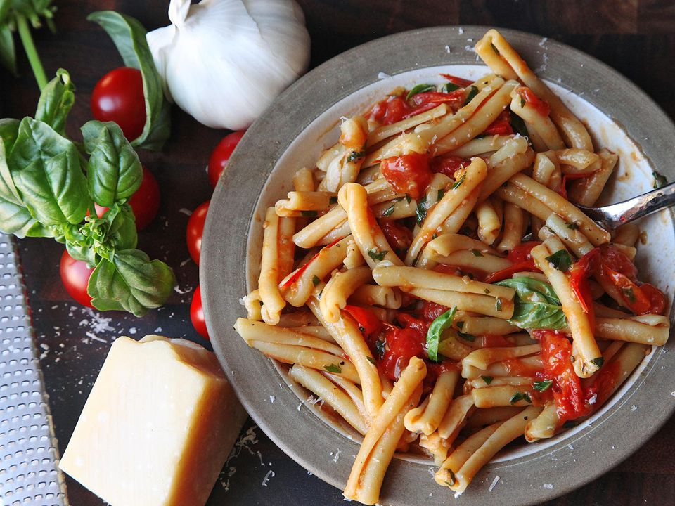 Overhead shot of plate of pasta with blistered cherry tomato and basil sauce