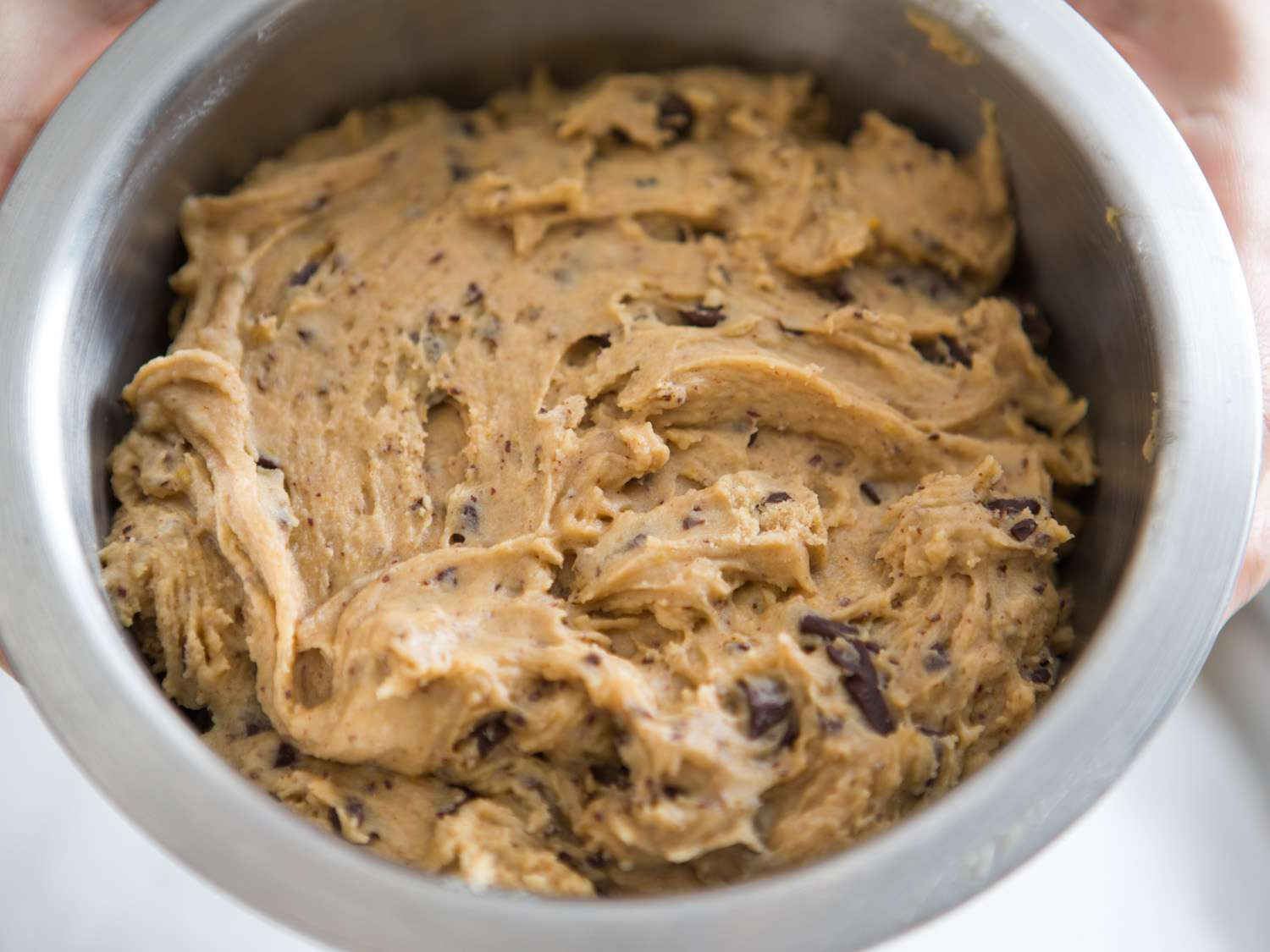 Chocolate chip cookie dough in a metal bowl going into the fridge to rest overnight before baking.