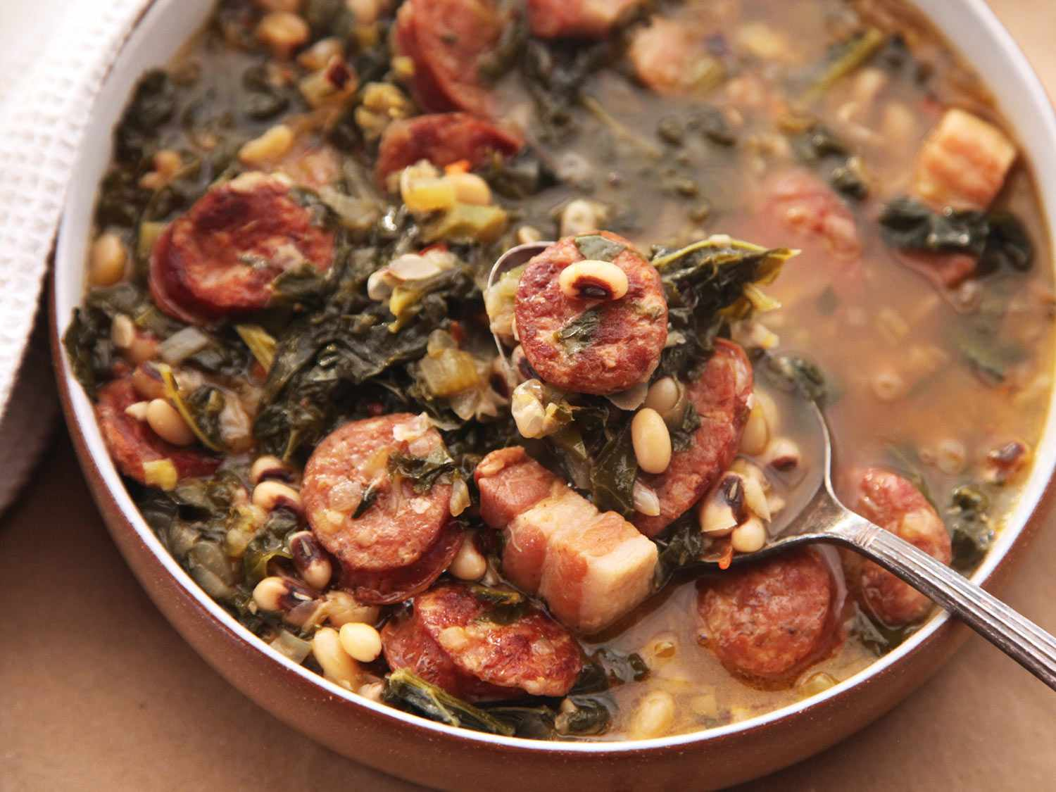 Hearty One-Pot Black-Eyed Pea Stew With Kale and Andouille, with a spoon holding some stew above the bowl.