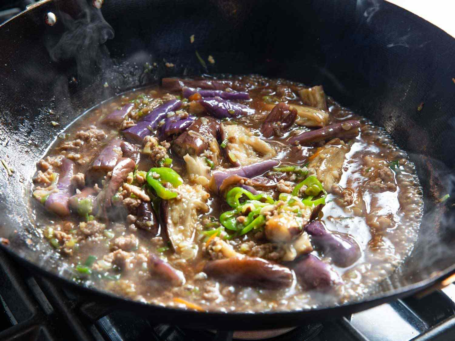 Sichuan eggplant simmering in a wok