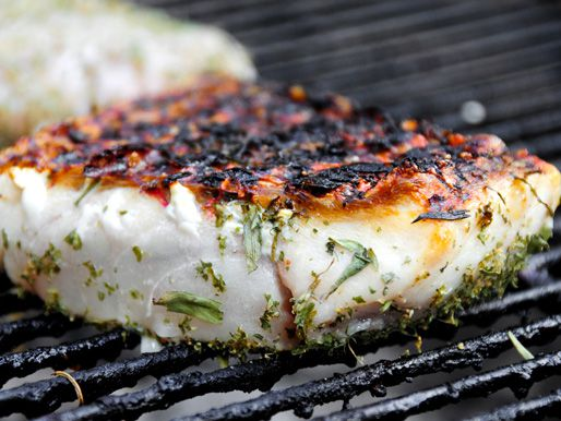 A fish fillet seasoned with herbs being cooked on the grill.