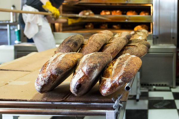 Loaves of bread on a baker's table in the kitchen at Tartine Bakery. In the background, someone is using a long handled peel to move loaves of bread in a commercial oven.