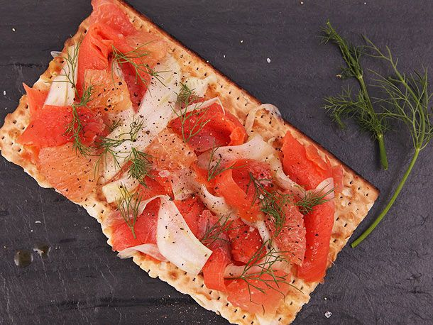 A piece of matzo layered with grapefruit suprèmes, shaved fennel, and smoked salmon, sprinkled with fennel fronds