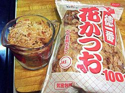 A glass measuring cup full of dried bonito flakes with a package of bonito flakes next to it.