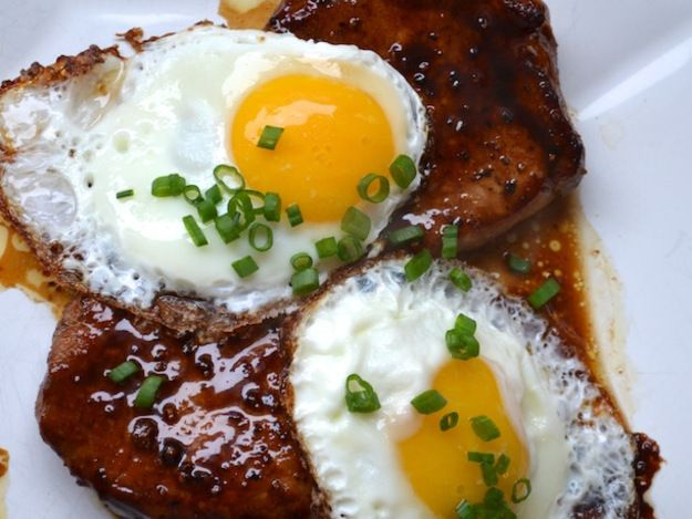 Bourbon Glazed Pork Chops with two fried eggs, and sliced chives on top.