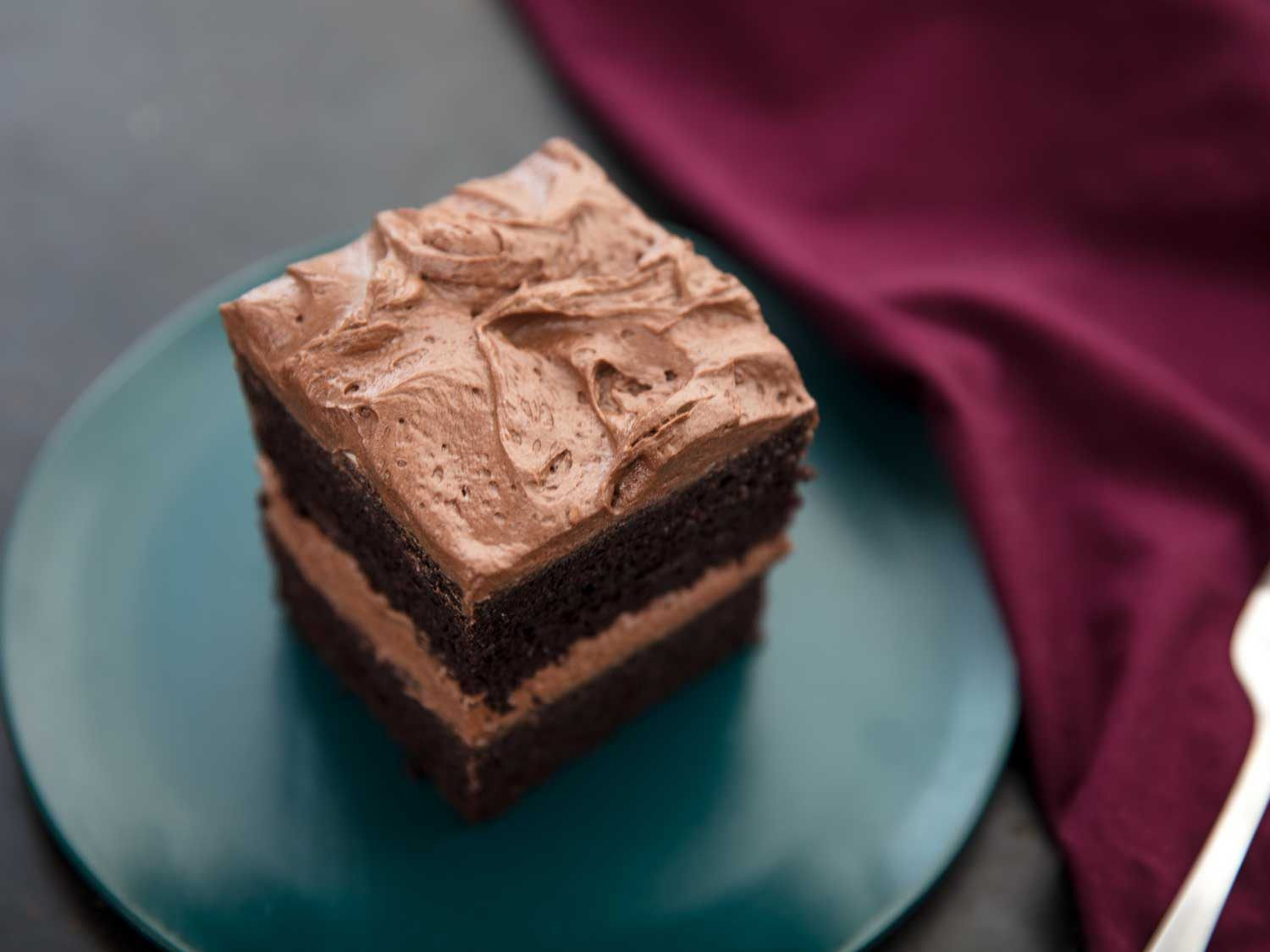 A square of double-layer chocolate cake frosted with creamy whipped chocolate frosting, on a green plate