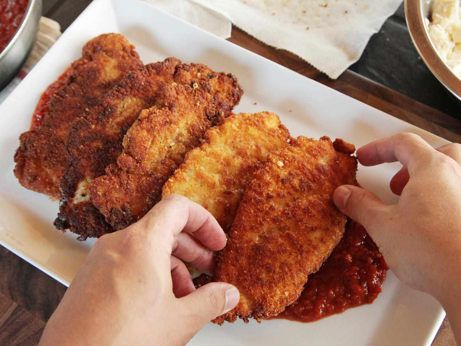 Laying down fried chicken breasts over red sauce