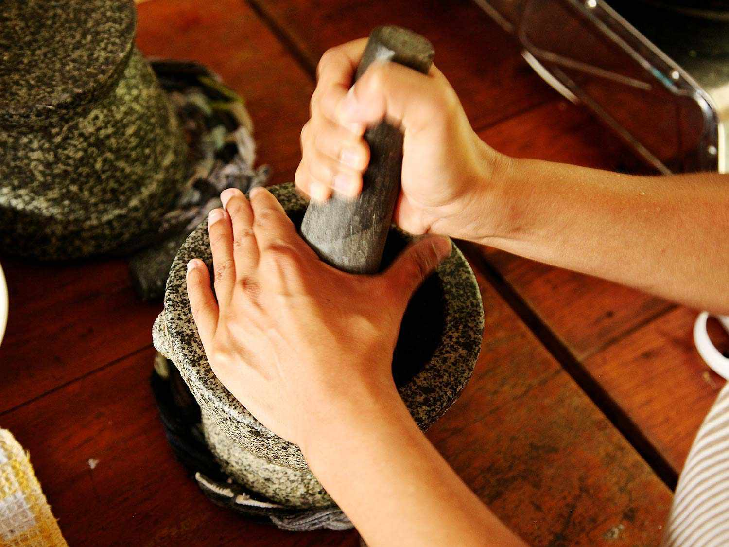 Hands pounding curry paste for Khao Soi Gai in a granite mortar and pestle.