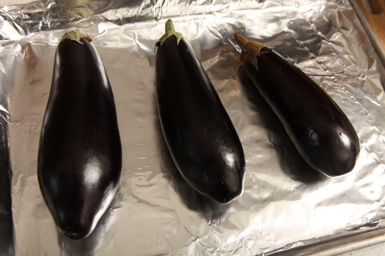 Three eggplants on a foil-rimmed baking sheet