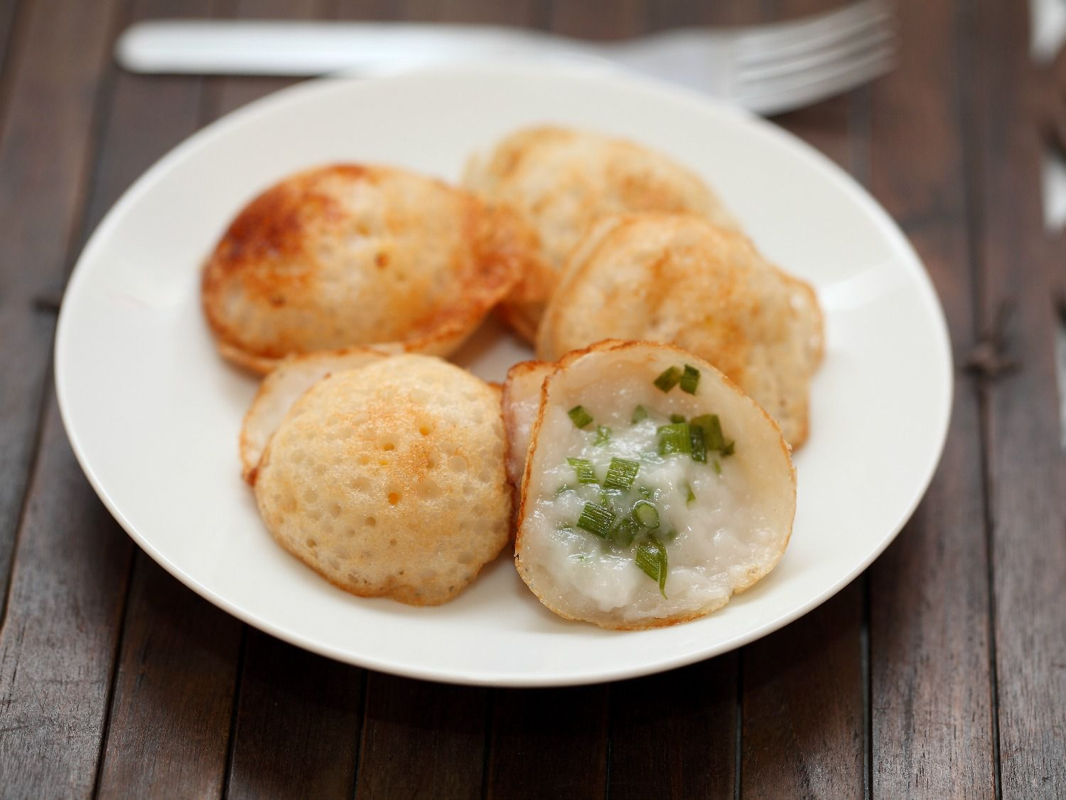 A white plate of serabi, small Indonesian pancakes made of rice flour and coconut.