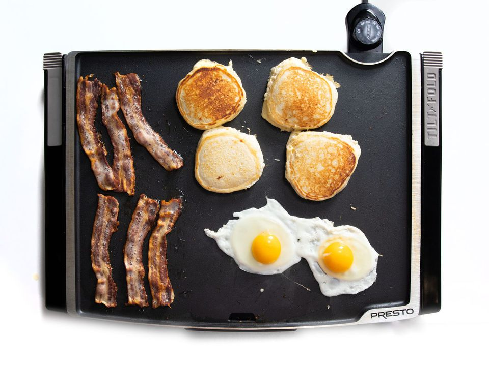 Overhead of cooking bacon, eggs, and pancakes on an electric griddle.