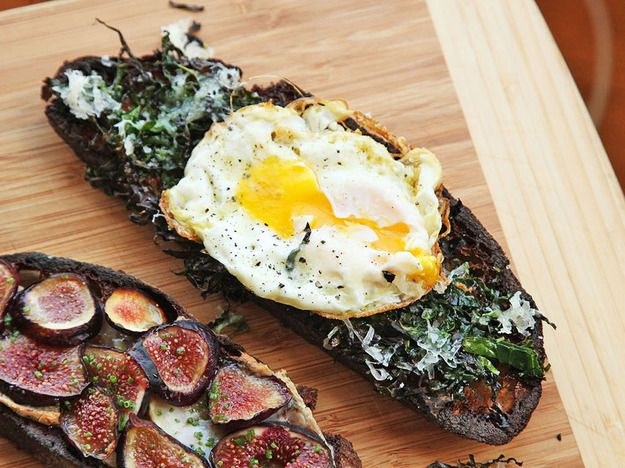 Kale, parmesan, and fried egg tartine. The egg yolk is broken. There is a fig tartine next to it.