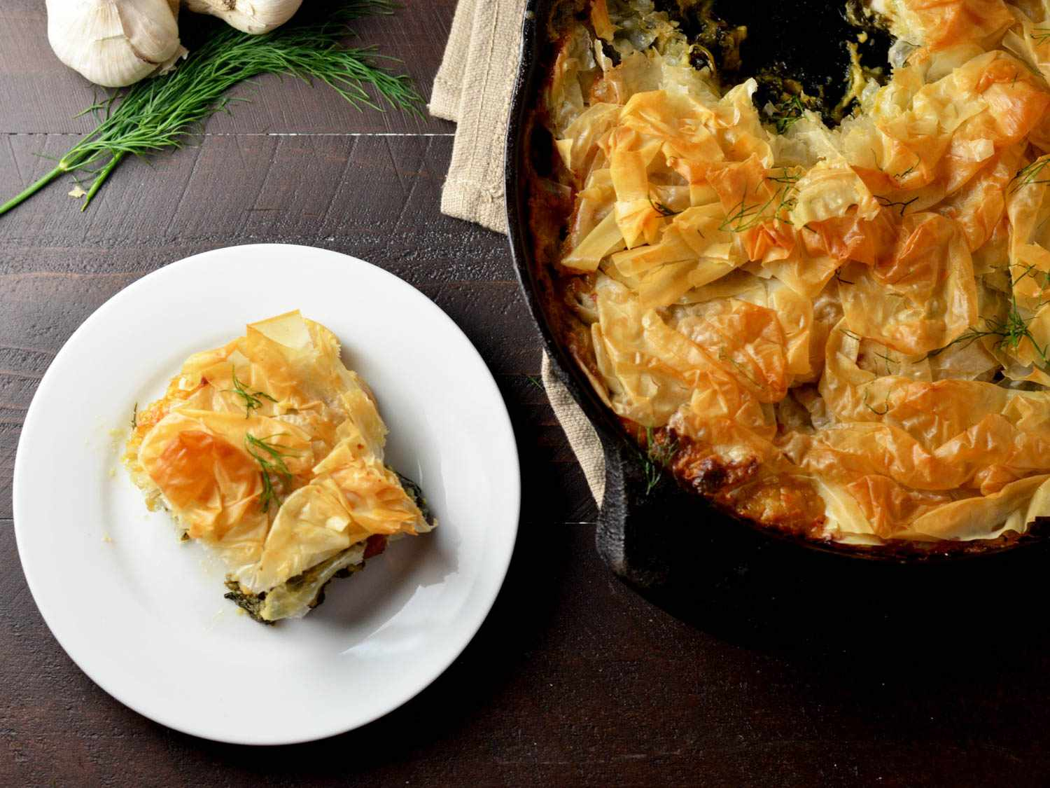 Creamy Garlic Chicken Spanakopita Skillet in a skillet, with a serving on a white plate next to the skillet.