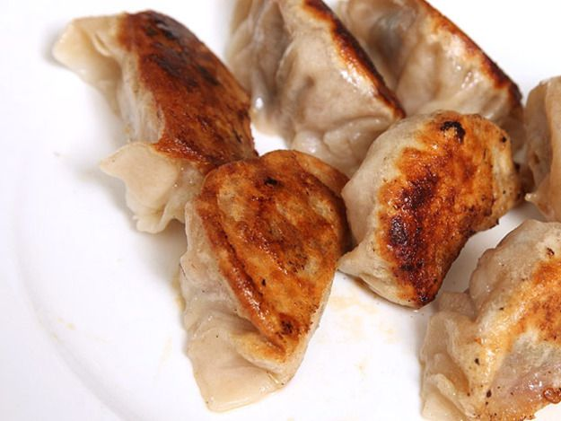 Seven pan-fried bacon and ramp dumplings on a plate.