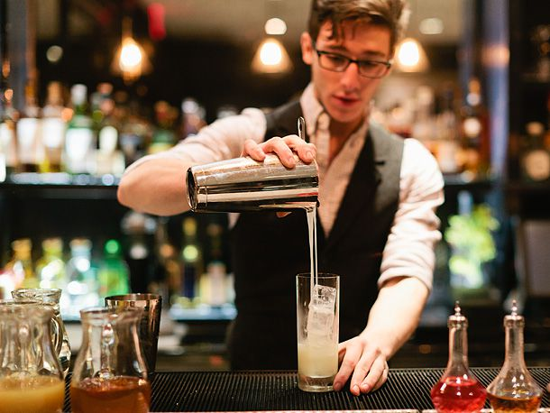 bartender straining and pouring a drink
