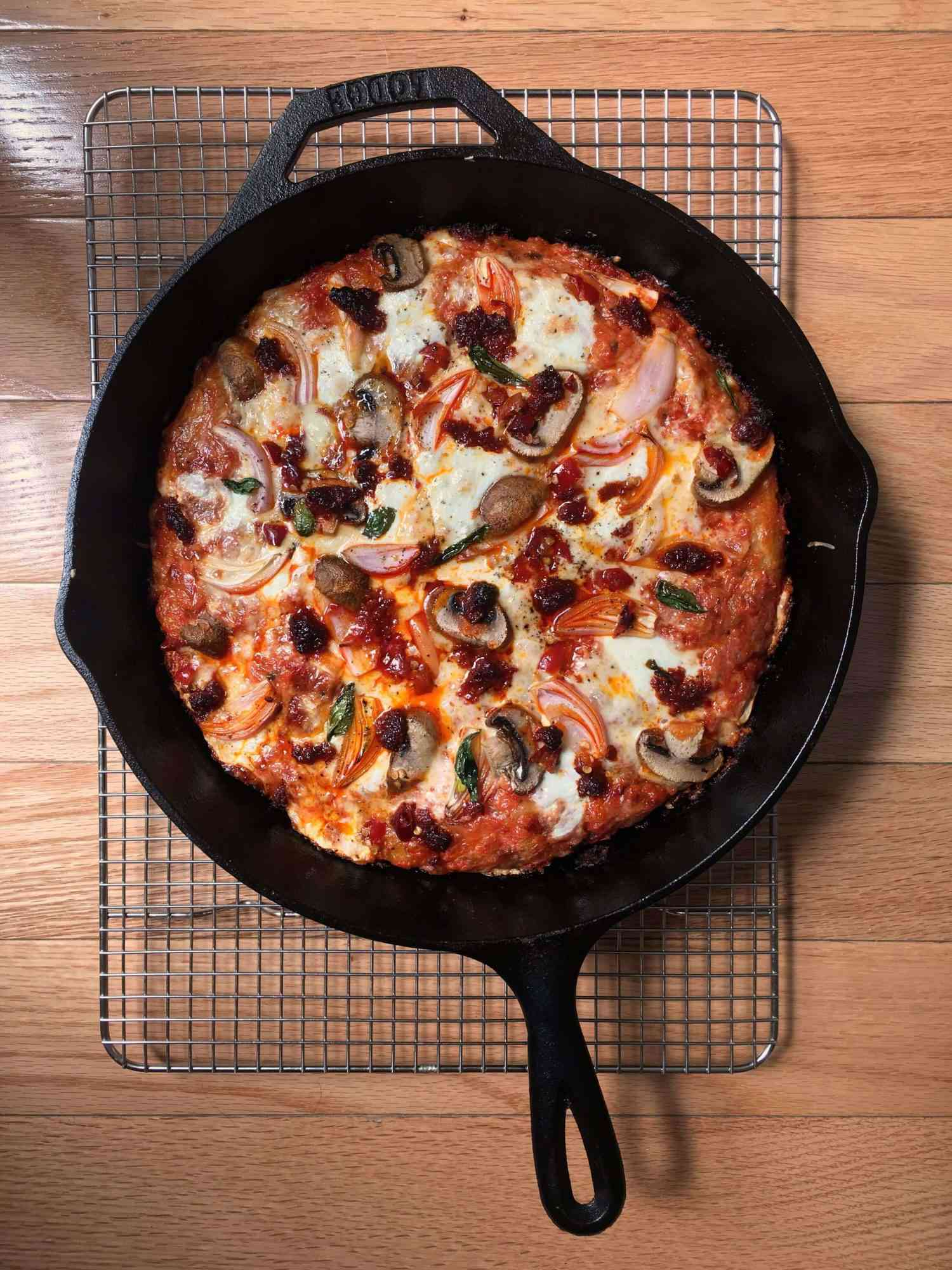overhead view of pan pizza in a cast iron skillet resting on a wire rack
