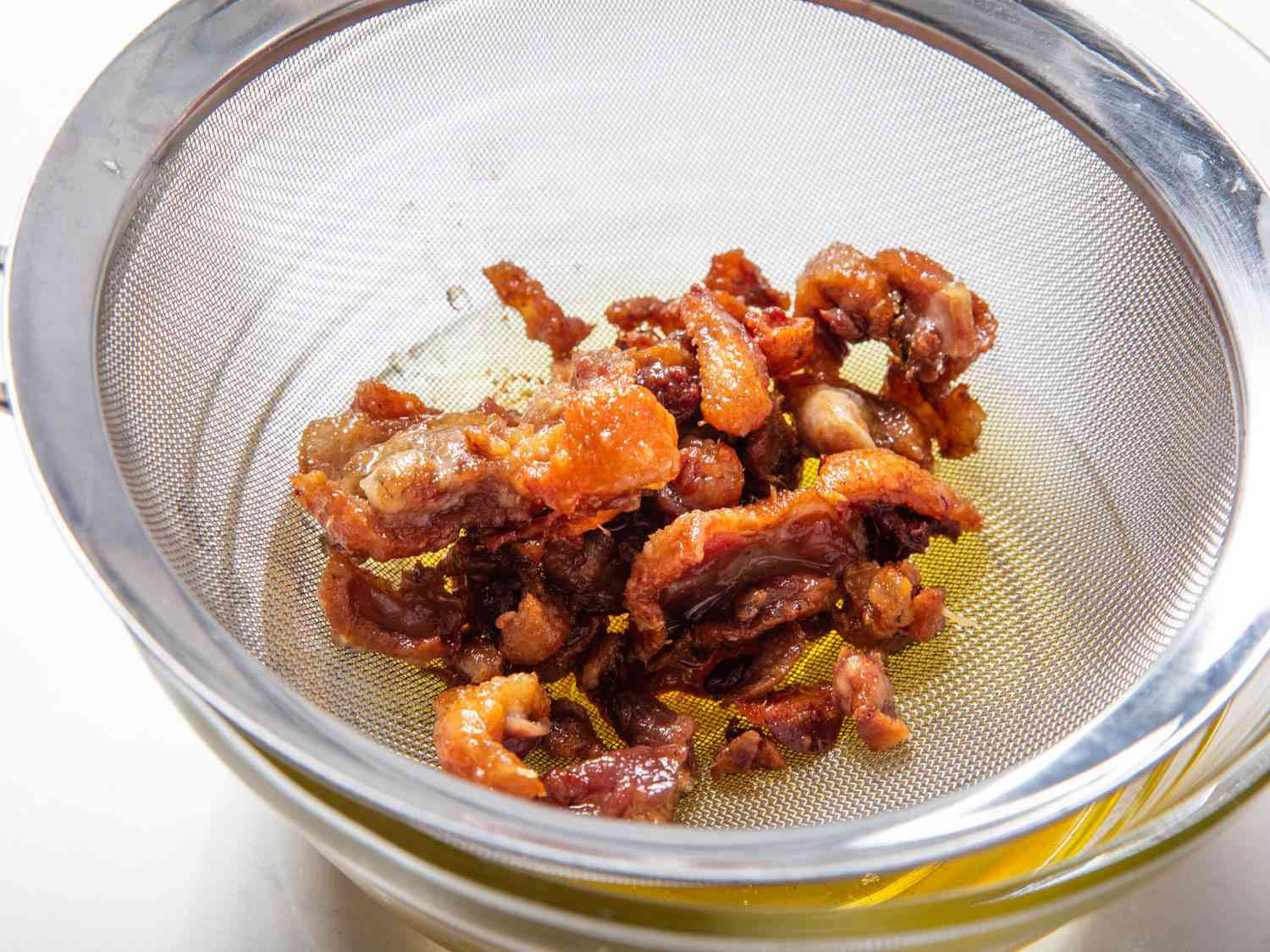 Duck cracklings in a fine-mesh strainer.