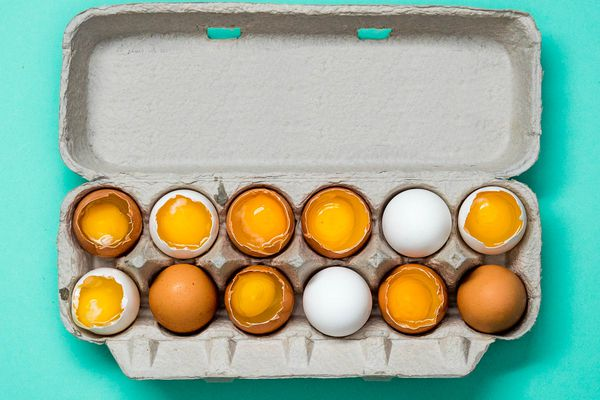 An open carton of a dozen eggs. Some of the eggs are cracked open so the yolks are exposed.