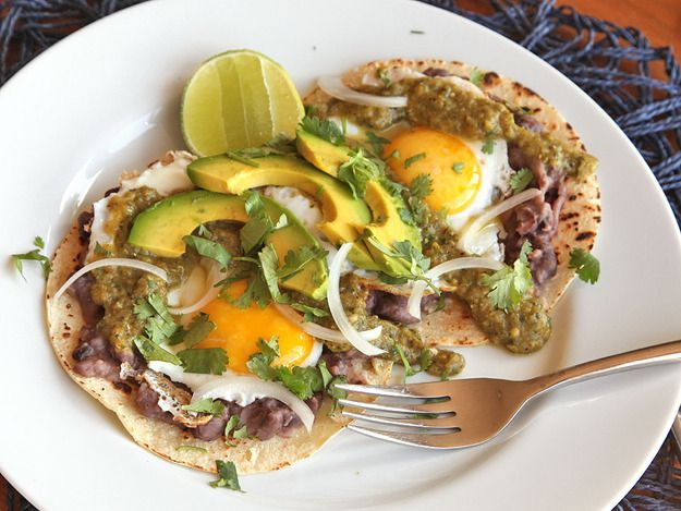 Huevos Rancheros Verdes, or Fried Eggs With Green Salsa and Refried Beans, on a plate with a fork and lime wedge.
