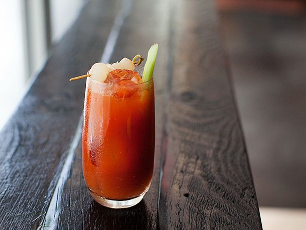 A Bloody Mary cocktail in a tall glass garnished with a celery stick and some shrimp on a toothpick.