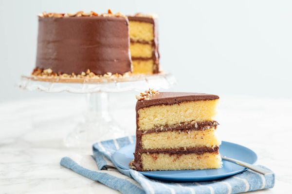 A slice of three layer almond cake with dark chocolate frosting on a blue plate, with the remainder of the cake on a white stand in the background