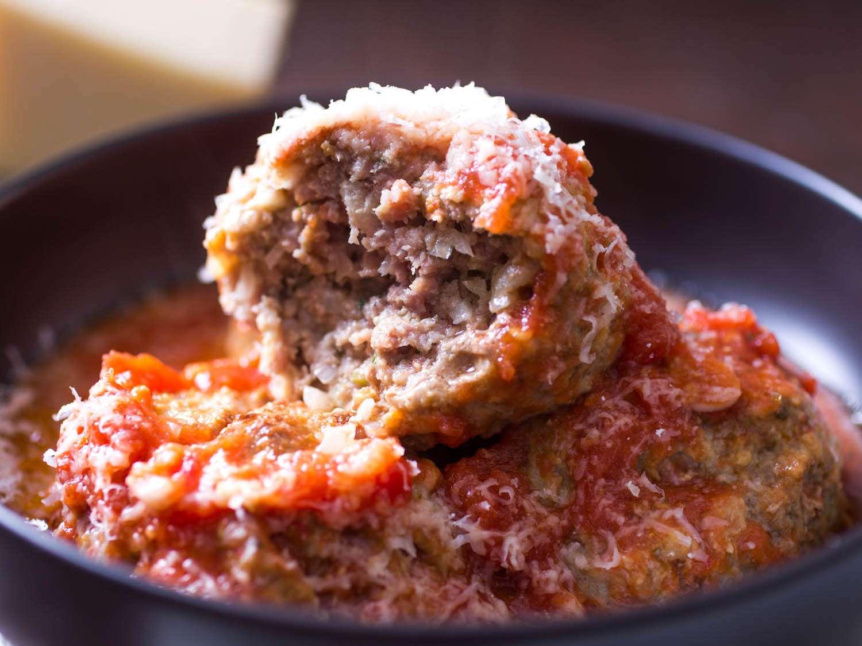 Breaking into an Italian-American meatball in red sauce in a dark bowl.