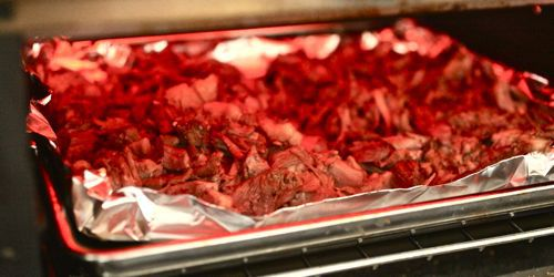 Broiling carnitas on a foil-lined rimmed baking sheet.