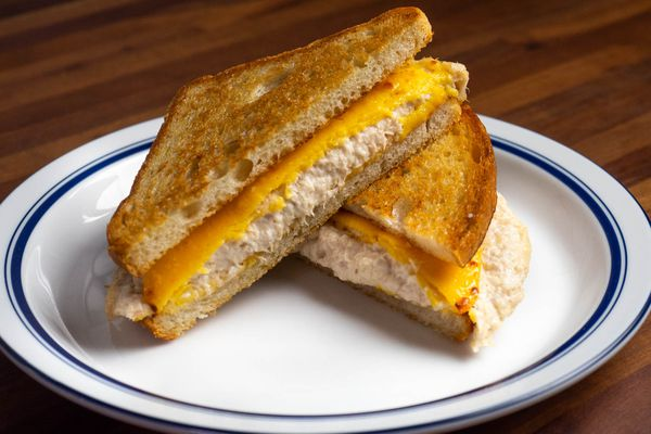 A tuna melt sandwich on a plate, cut in half diagonally to make triangles; showing melted yellow American cheese slices on top of a creamy tuna salad and nicely toasted bread.