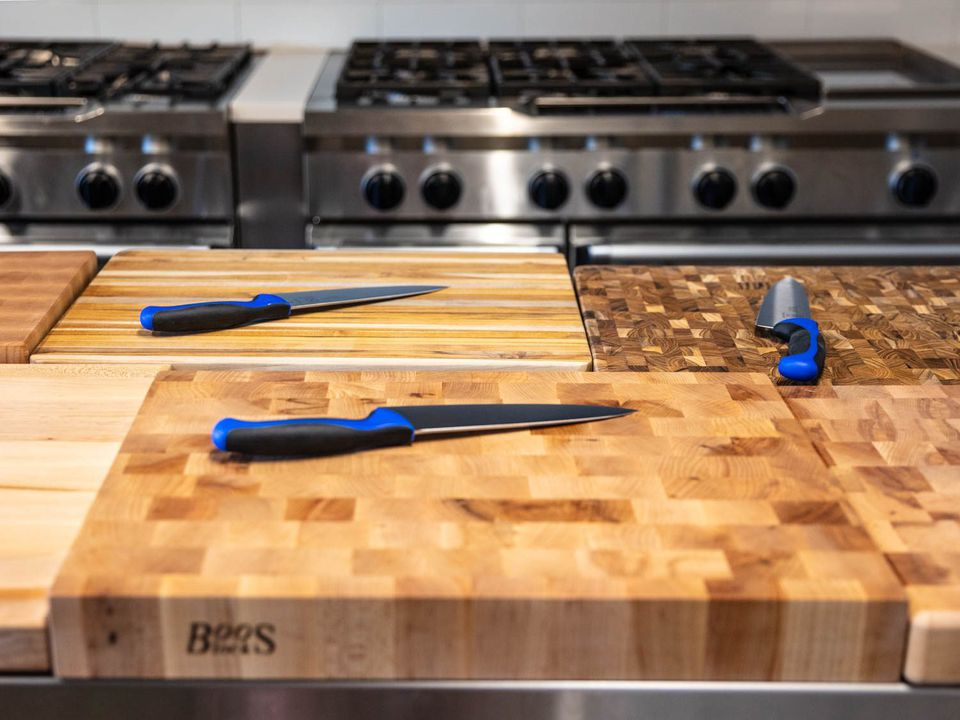 Several wooden cutting boards on a work table, with brand new chef's knives on top of each one.