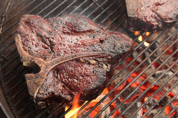 A cooked porterhouse steak on a hot grill.