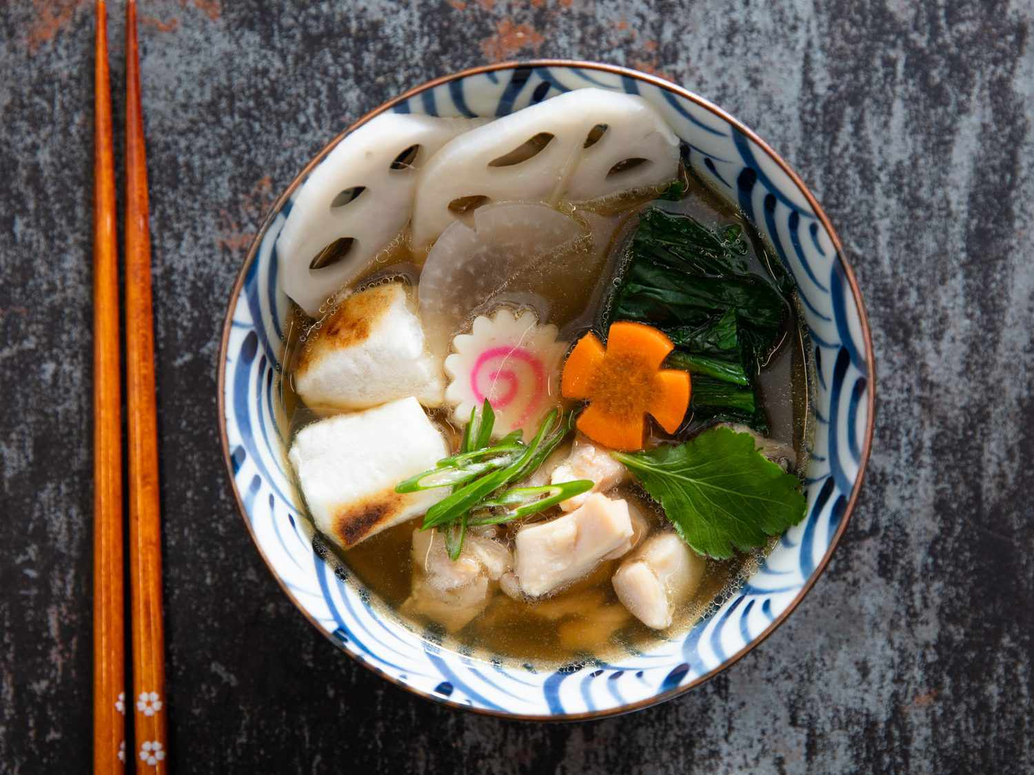 A bowl of ozoni (Japanese New Year's soup) filled with lots of goodies: tender carrots, lotus root, daikon radish, fish cake, chicken and more