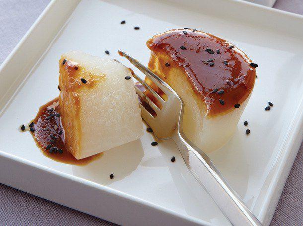 Braised daikon radish on a square plate, sprinkled with black sesame seeds.
