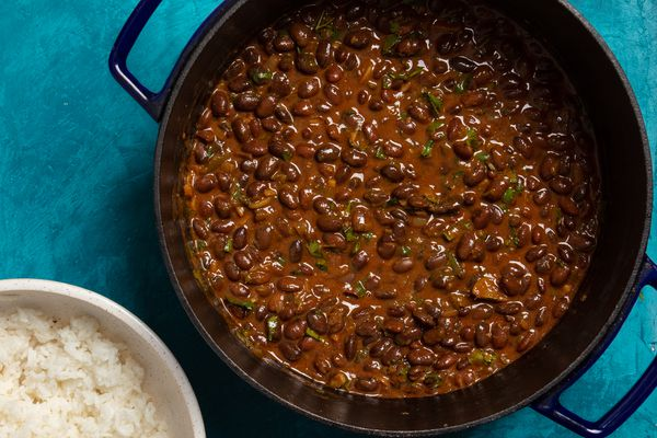 a dutch oven with Kenyan njahi beans in a coconut sauce with a bowl of white rice to the side