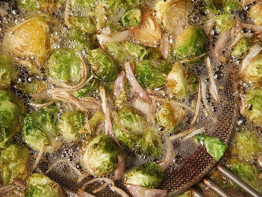 A metal spider scooping out golden-brown fried Brussels sprouts and shallots.