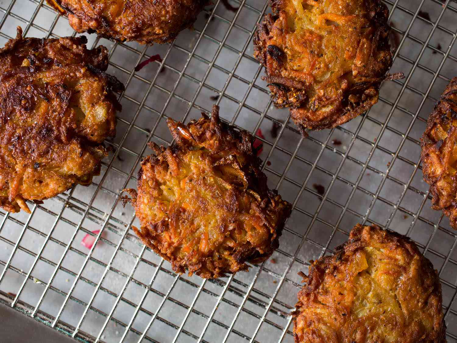 Fried sweet potato, squash, and carrot latkes resting on a wire rack
