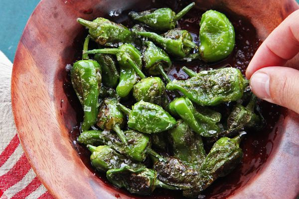 A small wooden bowl of grilled Padrón peppers sprinkled with salt.