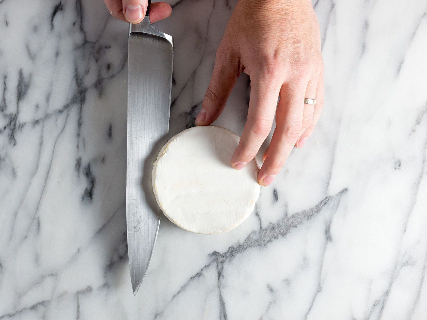 Slicing a round of brie in half.