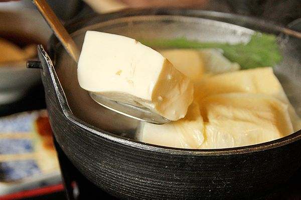 Yudofu (hot water tofu) being spooned out of a bowl.